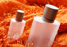 Cosmetic Bottles. Perfume bottle on fancy orange tassels color fabric royalty free stock photo