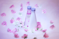 Cosmetic bottles with flowers. Cosmetic bottles with pink and white flowers stock photos