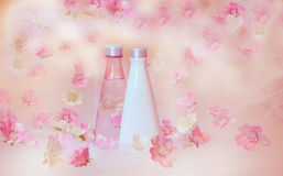 Cosmetic bottles with flowers. Cosmetic bottles with pink and white flowers Royalty Free Stock Images