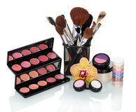 Cosmetic brush, eyeshadow, blush, lip gloss and orchid flower isolated. Royalty Free Stock Image