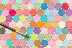 Cosmetic brushe laying on colored eye shadows top view royalty free stock photo