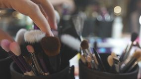 Cosmetic Brushes in Cup. Various sets of cosmetic brushes in black cups on the table against blurred background stock video footage