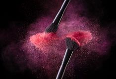 Cosmetic Brushes And Explosion Colorful Powders. Close Up Of Makeup Soft Blush Brushes Releasing Cloud Of Red Powder Splash On Black Background. Makeup Tools royalty free stock image