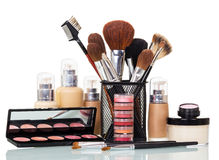 Cosmetic brushes, liquid foundation, lip gloss, blush, cream bank isolated. Stock Photos