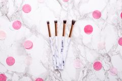 Cosmetic brushes with pink decorations on a marble background stock images