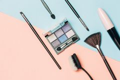 Cosmetic and brushes set on pink and blue background royalty free stock images