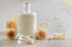 Cosmetic care. Cosmetic liquid, maybe milk, shampoo or toner, in glass bottle decorated with roses Royalty Free Stock Images