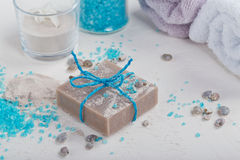 Cosmetic clay powder, homemade clay soap and blue sea salt on wh Stock Photos