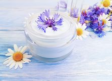 Cosmetic cream, chamomile flower, cornflower on a wooden background royalty free stock images
