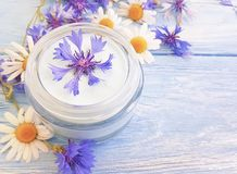 Cosmetic cream, chamomile beauty hygiene relaxation flower, cornflower on a wooden background royalty free stock photos