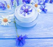 Cosmetic cream, chamomile relaxation flower, cornflower on a wooden background stock image