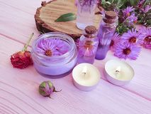 Cosmetic cream, chrysanthemum flower on a pink wooden background, candle stock images