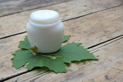 Cosmetic cream with grape leaf stock photos