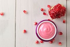 Cosmetic cream in a lilac jar and with fresh pomegranate on a white wooden table. pomegranate extract. cosmetics. Top view stock photo