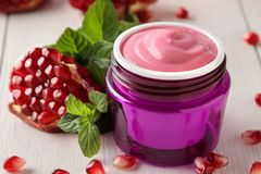 Cosmetic cream in a lilac jar and with fresh pomegranate on a white wooden table. pomegranate extract. royalty free stock image