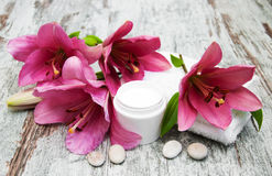 Cosmetic cream and pink lily flower Royalty Free Stock Photo