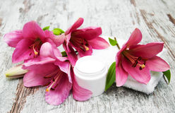 Cosmetic cream and pink lily flower Royalty Free Stock Images