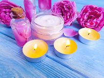 Cosmetic cream, pink rose extract on wooden background, candle. Cosmetic cream, pink rose extract wooden background, candle stock photo