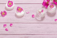 Cosmetic cream with pink roses on wooden table Royalty Free Stock Image