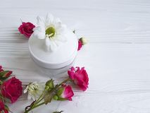 Cosmetic cream with roses on a white wooden background. Cosmetic cream with roses a white wooden background Royalty Free Stock Images