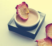 Cosmetic cream surrounded by petals Royalty Free Stock Photo