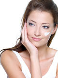 Cosmetic cream on women face. Beautiful woman with moisturizer cosmetic cream on face - on a white Royalty Free Stock Images