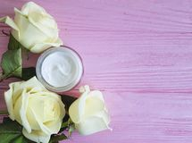 Cosmetic hand cream anti aging , decorated yellow rose skin careon a pink wooden. Cosmetic cream, yellow rose on a pink wooden skin care  anti aging, decorated Stock Photo