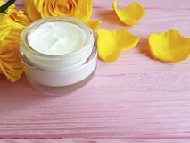 Cosmetic cream anti aging, product, decorated yellow rose skin careon a pink wooden. Cosmetic cream, yellow rose on a pink wooden skin care rustic anti aging Stock Image