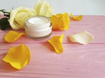 Cosmetic hand cream anti aging, product, decorated yellow rose skin careon a pink wooden. Cosmetic cream, yellow rose on a pink wooden skin care rustic anti Stock Photos