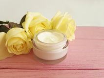 Cosmetic cream, yellow rose  skin careon a pink wooden. Cosmetic cream, yellow rose on a pink wooden skin care rustic Royalty Free Stock Photo