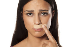 Cosmetic disaster. Young brunette put the patch under her nose because of bad waxing her mustache stock image