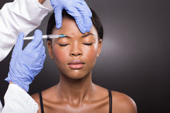 Cosmetic doctor injecting forehead Stock Image