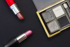 Cosmetic eyeshadow and lipstick on a black background. Abstract composition of cosmetics royalty free stock photography