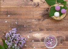 Cosmetic flat lay with a bouquet flowers lilac. Spa handmade raging bombs and hydrogel balls on wooden slice on brown wooden backg. Round stock images