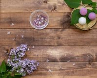 Cosmetic flat lay with a bouquet flowers lilac.Spa handmade raging bombs and hydrogel balls on wooden slice on brown wooden backg. Cosmetic flat lay with a stock photography