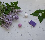 Cosmetic flat lay with a bouquet flowers lilac.Spa handmade raging bombs and lavender soap on grey concrete background. Cosmetic flat lay with a bouquet flowers royalty free stock image