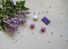 Cosmetic flat lay with a bouquet flowers lilac.Spa handmade raging bombs and lavender soap on grey concrete background. Cosmetic flat lay with a bouquet flowers royalty free stock photography