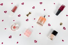 Cosmetic flat lay - perfume, nail polish, lipstick, small gift box, golden accessories on white background with tiny red hearts am royalty free stock photography