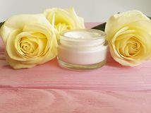 Cosmetic hand cream anti aging, product anti aging , decorated yellow rose skin careon a pink wooden. Cosmetic cream, yellow rose on a pink wooden skin care Royalty Free Stock Image