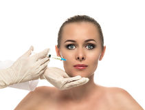 Cosmetic injection to the pretty Beautiful woman face and beautician hands with syringe. Royalty Free Stock Photo