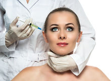 Cosmetic injection to the pretty Beautiful woman face and beautician hands with syringe. Stock Images