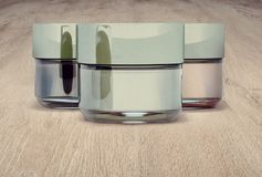 Cosmetic jars of clay, on wooden background. Three jars closed. Stock Photos