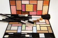 Cosmetic kit. Various make-up brushes with colorful make-up kit Stock Image