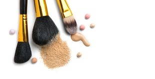 Cosmetic liquid foundation or cream, loose face powder, various brushes for apply makeup. Make up concealer smear and powder royalty free stock image