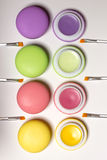 Cosmetic macaroons lying in row, balms, white background, lip brushes stock images