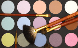 Cosmetic make-up background - eyeshadow and brush Stock Images