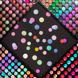 Cosmetic make-up palettes background with scattered colorful confetti. Flat lay. Top view. Crop image stock images