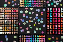 Cosmetic make-up palettes with scattered colorful confetti on black background. Flat lay stock photo