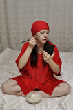 Cosmetic mask. Lady in red making herself cosmetic mask using brush Royalty Free Stock Photos