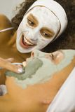 Cosmetic mask. Happy young women lying on towel putting puryfing mask Royalty Free Stock Photos